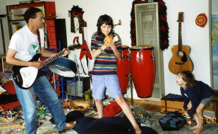 a June 2000 photo of Peter playing my Fender Venus, my son Sam playing a pumpkin shaker, a bone shaker and some bells, and my son Arthur playing electronic drums
