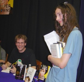 John Green autographs Arthur's copies of his books