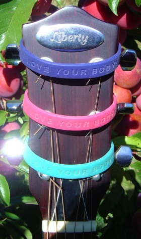 The 'Love Your Body!' wristbands from the Love Your Body! Wristband Project, being modeled by the headstock of my Liberty 'shooting stars' resonator guitar