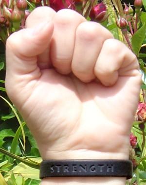 a black 'Strength' wristband